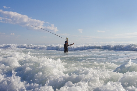 beach fisherman casting into the surf