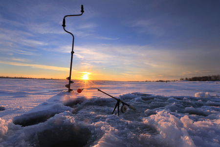 drill, fishing rod near hole on the ice in winter river