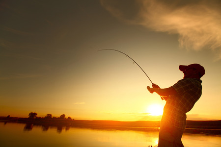 man fishing shallow waters in lake at sunset