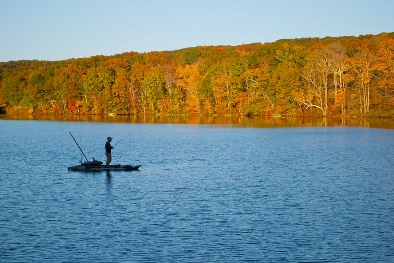 man fishing connecticut lake from kayak