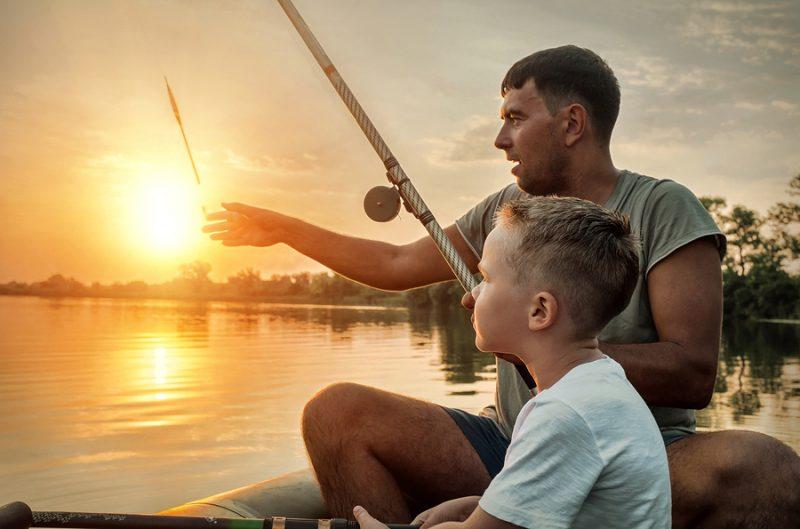 father teaching son to fish on lake-family bonding through fishing